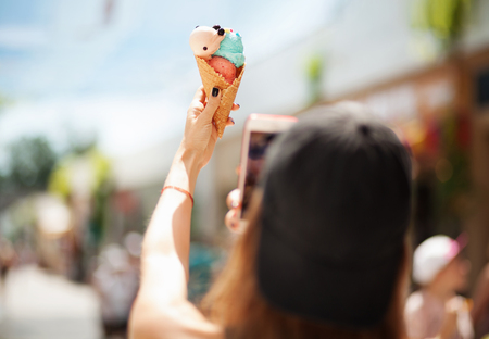 Pretty girl taking picture of ice cream on smartphone. Focus on ice cream photo