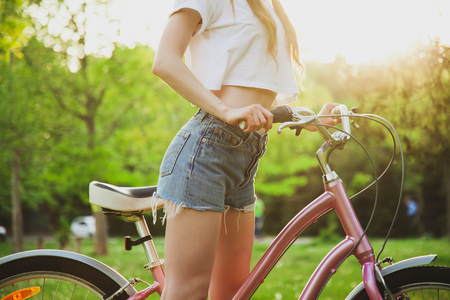 Beautiful woman with bicycle on the meadow in the park. Closeup picture