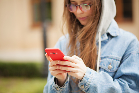 Outdoor picture of a young lovely woman with smartphone. Focus on a hands holding smartphone