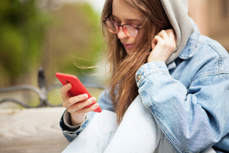 Outdoor picture of a young lovely woman with smartphone. Focus on a hand holding smartphone