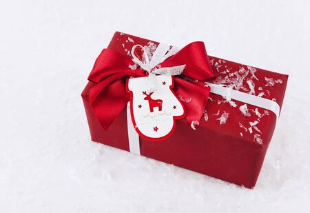 Christmas gift box with a bow wrapped in red surrounded by artificial snow Stock Photo