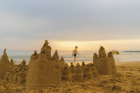 Children build beautiful sand castle on the sea shore. Sandcastle is close up and a large one, boy is on the background