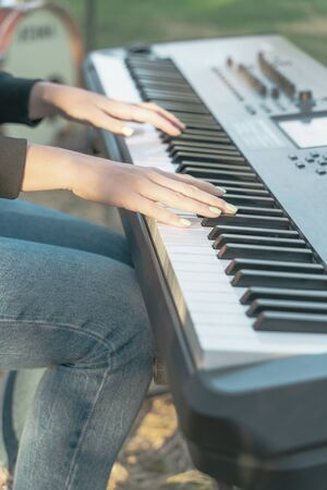Girl plays piano keyboard, hands close up, vertical image