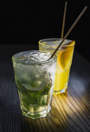Non-alcoholic mojito with ice in weeping glass with eco-friendly bamboo straw on wooden table in the foreground. Fruit cocktail with orange slice and eco small tube on the background. Plastic free and zero waste concept