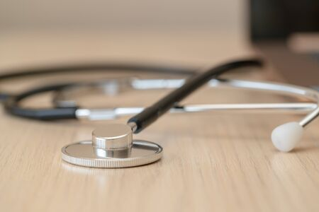 Macro black stethoscope on light brown desk, close up picture. Laptop is on the background. Horizontal image