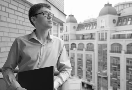 Serious young man, financial specialist, in glasses standing outdoors on balcony in city center with laptop and looking thoughtfully. Deliberate decision concept. Black-and-white image.