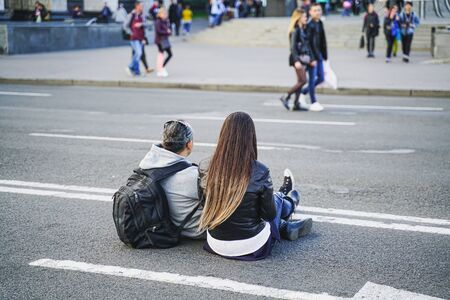 Couple man and woman have a rest in the city centre on a day off in spring. They are sitting on the traffic way in downtown during week-end