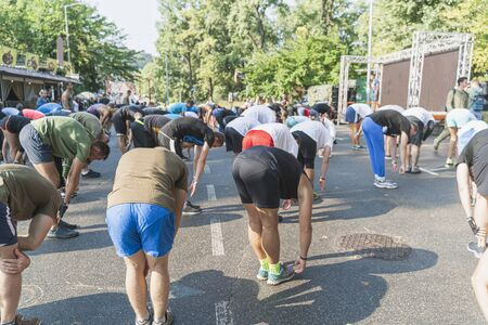 Adults are doing physical exercises in the park, Kiev, Ukraine. Group sport activities outdoors in summer to maintain health. Sport for all ages concept.