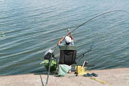 Senior adult man on the river bank casting the fishrod. Fishman is sitting in the chair surrounded by fishing equipment, Ukraine. Color image with copy space. Lifestyle concept.