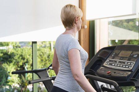 Middle aged woman exercising on treadmill in gym. Health club with nature view on green trees on sunny day. Color image with copy space.
