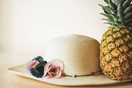 Straw hat and pineapple symbolize traveling to warm tropical countries. Color image, travel concept.