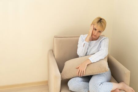 Woman stay at home, sitting in armchair, feeling sick, fever heat and depression of strength. Color image.