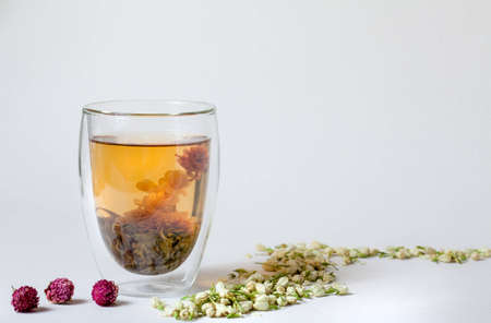 Flowering Tea in Transparent Glass and Dry Tea Flowers photo