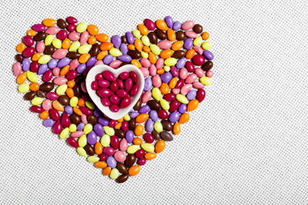 Colorful Glazed Candies Heart on White Background photo