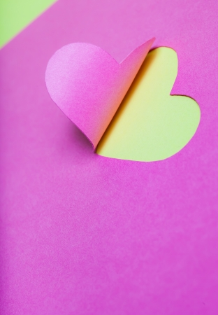 Heart Half-Cut From Pink Paper with Yellow Background photo