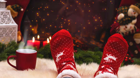 Red knitted socks against the background of New Year's decorations and fireplace, Christmas tree garland. Cozy winter evening by the fireplace, blurred background. New Year and Christmas festive Imagens