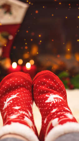 Red knitted socks against the background of New Years decorations and fireplace, Christmas tree garland. Cozy winter evening by the fireplace, blurred background. New Year and Christmas festive