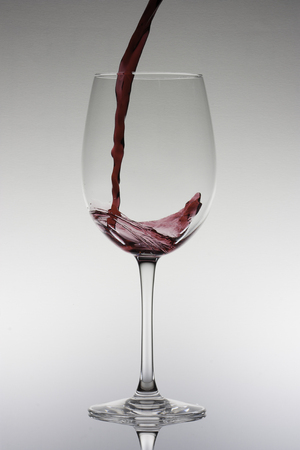 Pooring a red wine in a glass Stock Photo