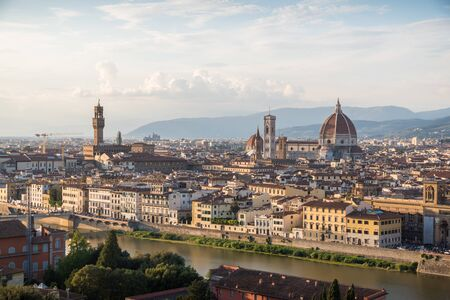 Florence panoramic view from above during a colorful summer sunset with lights sun historical buildings Duomo tower of Palazzo Vecchio churches and Ponte Vecchio