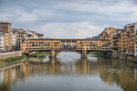 Ponte Vecchio in historical center downtown in Florence during sunrise with historical old buildings and water reflections in Arno river