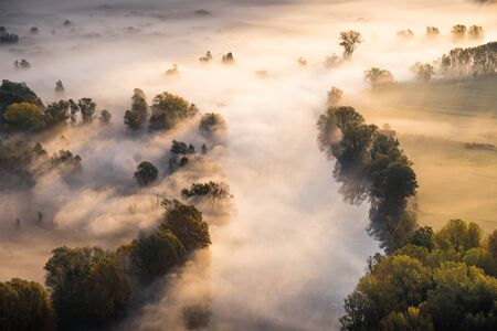 Airuno on Adda river in Northern Italy at sunrise with myst fog coloured trees foliage in autumn fall season Reklamní fotografie