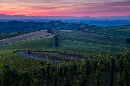 Amazing red and purple sunset over Oltrepo Pavese hills with wineyards and country roads