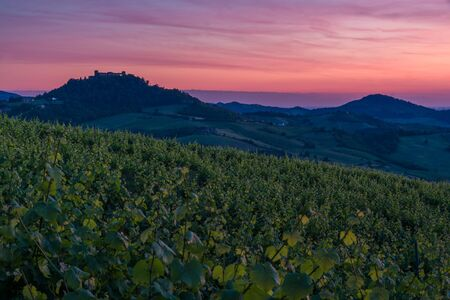 Amazing red and purple sunset over Oltrepo Pavese hills with wineyards and country roads and Montalto Pavese castle in the background