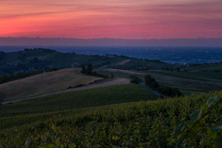 Amazing red sunset over Oltrepo Pavese hills with wineyards and country roads