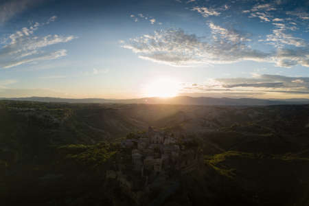 Aerial view of stone town Civita di Bagnoregio with the sun at the sunrise with clay badlands and trees in the background