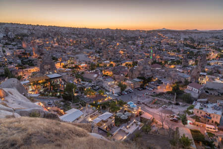 Panorama of Goreme at the blue hour with fairy chimneys, artificial lights and rock formations