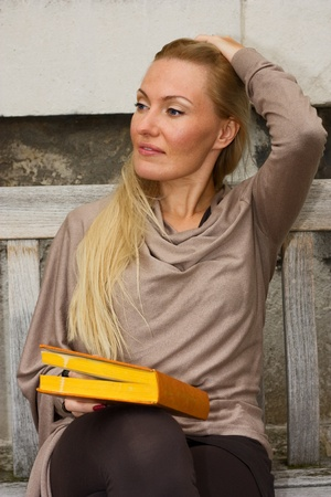 woman sitting on a bench holding a book. photo