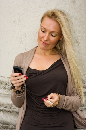cell phone addiction: young woman smiking and looking at her mobile phone.