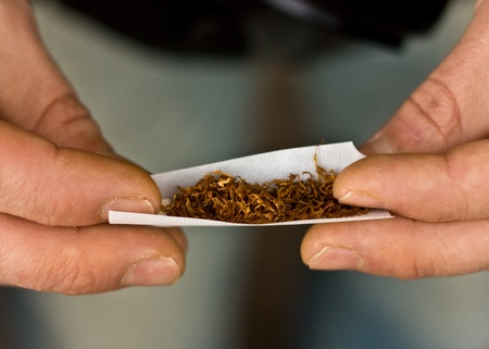 a closeup of hands rolling tobacco.  photo