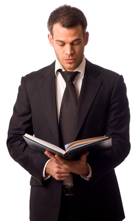 man holding book: a young business man holding a book.