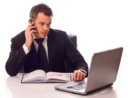 businessman phone: business man working at a desk.  Stock Photo