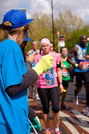LONDON - APRIL 22: Volunteer giving water to runners at the London marathon on April 22, 2012 in London, England, UK. The marathon is an annual event. Stock Photo - 13537179