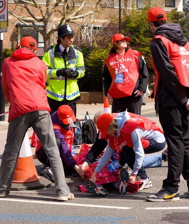 LONDON - APRIL 22: Unidentified person gets treated by first aiders during the London marathon on April 22, 2012 in London, England, UK. The marathon is an annual event.