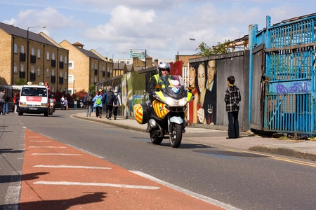escorting: LONDON - APRIL 22: security patrol in front of the lead car during the London marathon on April 22, 2012 in London, England, UK. The marathon is an annual even