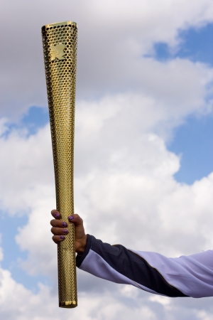 olympic symbol: London-July 21st: Unidentified torch bearer holds up the olympic torch on the 21st July 2012. The Olympics is a major sporting event around the world. Editorial