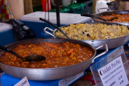 indian cookery: chicken piri-piri stew being served in the street