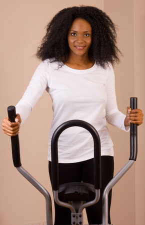 crosstrainer: young woman exercising at home. Stock Photo