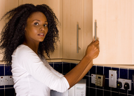 a young woman opening a kitchen cupboard. Stock Photo