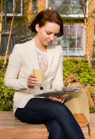 young woman reading paper and drinking coffee. photo