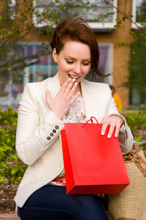 touched: young woman looking at a gift in a bag Stock Photo