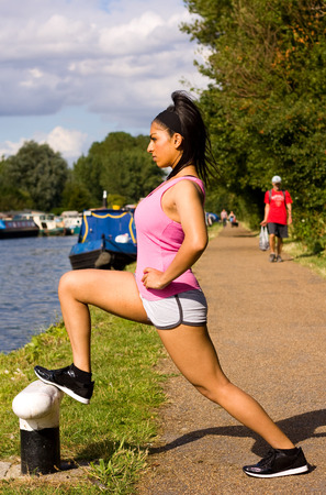young woman exercising on the canal path photo