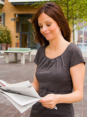 a young woman reading the newspaper.  photo