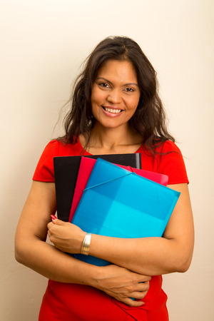 latina girl: beautiful latina holding folders.  Stock Photo