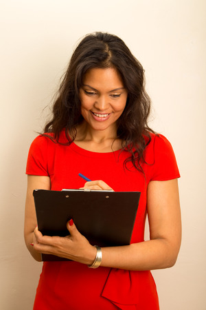latina girl: young woman writing on a clipboard. Stock Photo