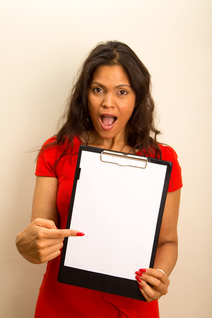 young woman looking surprised showing a clipboard. photo