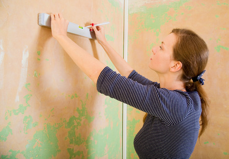 competent: young woman using spirit level.
